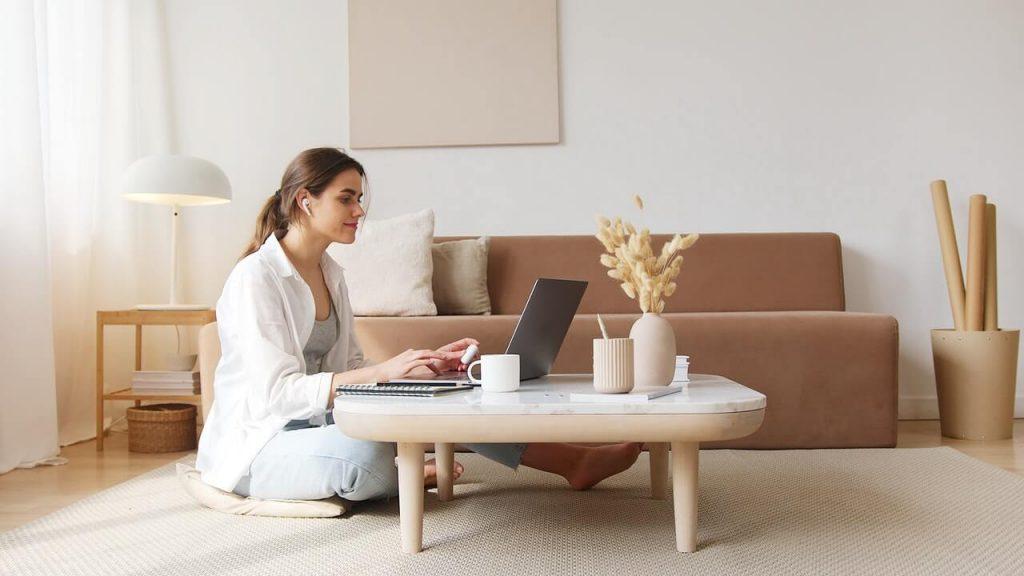 Ogrzewanie podłogowe. Kobieta siedząca na ciepłej podłodze w salonie